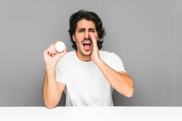 Young man holding a moisturizer shouting excited .