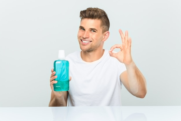 Young man holding a mouthwash cheerful and confident showing ok gesture.