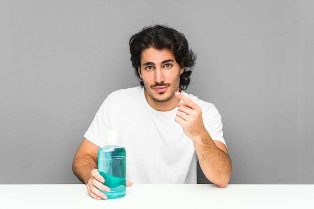 Young man holding a mouthwash pointing with finger at you as if inviting come closer