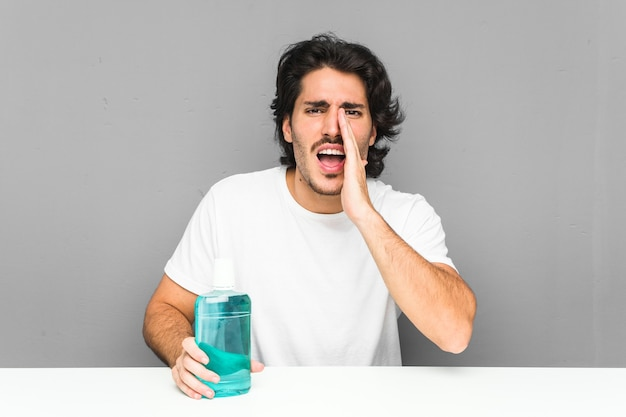 Young man holding a mouthwash shouting excited to front.