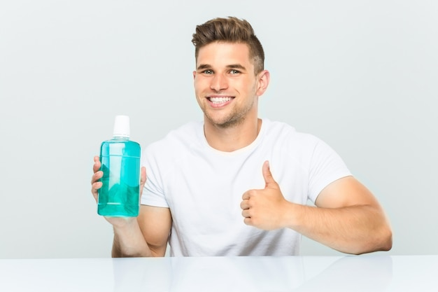 Young man holding a mouthwash smiling and raising thumb up