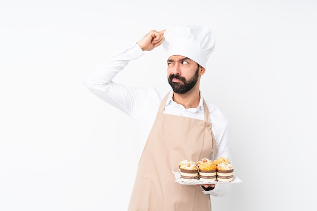 Young man holding muffin cake having doubts while scratching head