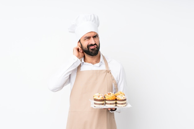 Young man holding muffin cake having doubts