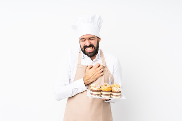 Young man holding muffin cake having a pain in the heart