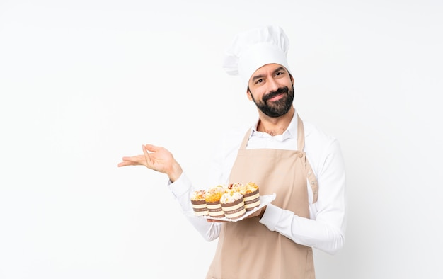 Young man holding muffin cake over isolated  extending hands to the side for inviting to come