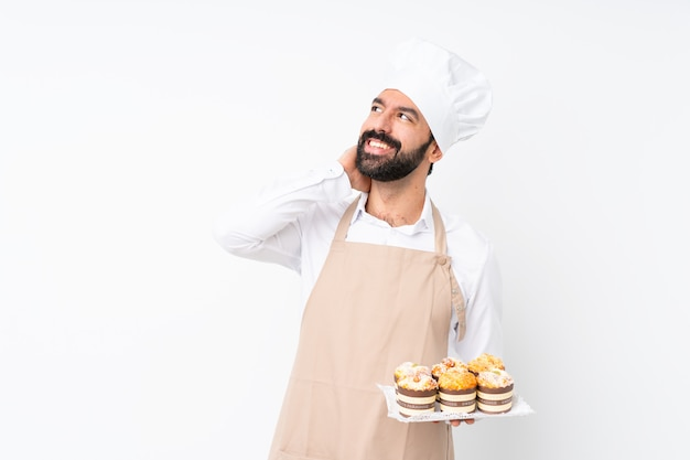 Young man holding muffin cake over isolated  thinking an idea