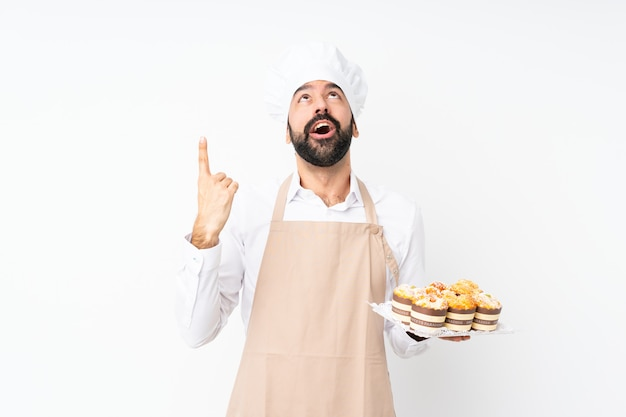 Young man holding muffin cake over isolated white  surprised and pointing up
