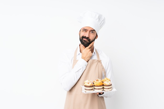 Young man holding muffin cake over isolated white  thinking