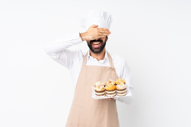 Young man holding muffin cake over isolated white wall covering eyes by hands