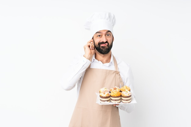 Young man holding muffin cake over isolated white wall frustrated and covering ears