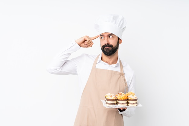 Young man holding muffin cake over isolated white wall having doubts and thinking