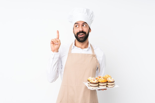 Young man holding muffin cake over isolated white wall thinking an idea pointing the finger up