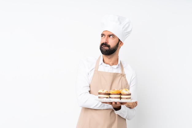 Young man holding muffin cake over isolated white with confuse face expression