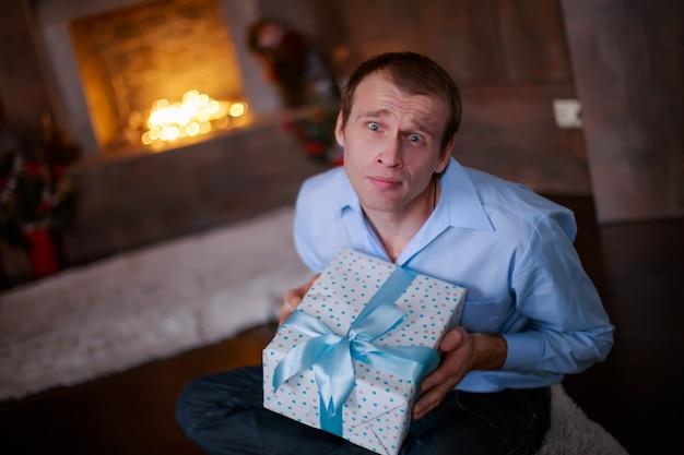 크리스마스 남자를 위한 새해 선물을 들고 있는 젊은 남자가 선물 상자를 준다