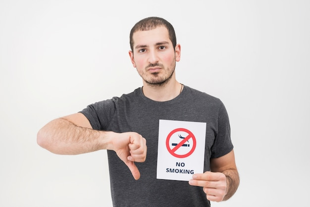 A young man holding no smoking sign showing thumbs down against white background