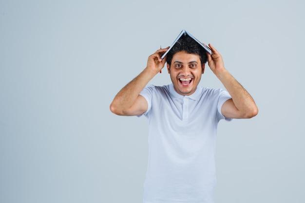 白いtシャツとジーンズで両手でノートを頭に抱えて幸せそうに見える若い男、正面図。
