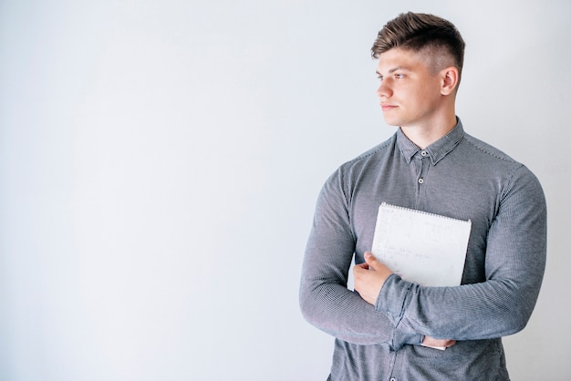 Young man holding notebook in studio