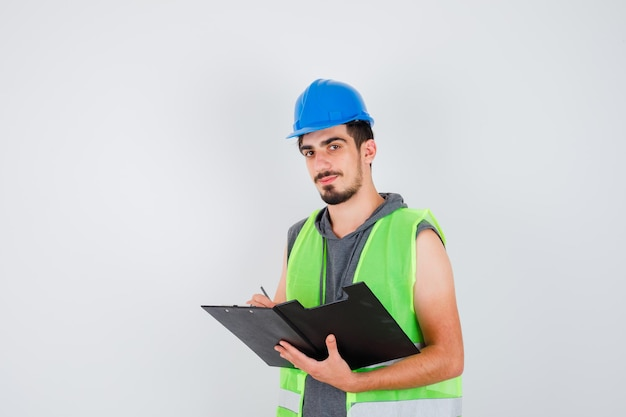Young man holding notebook and writing something on it with pen, looking at camera in construction uniform and looking happy