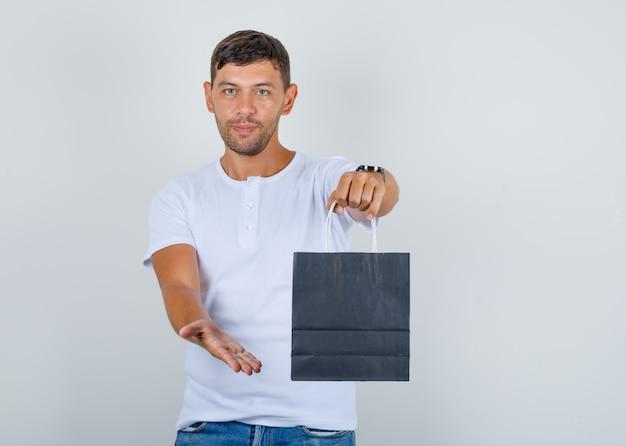 若い男が白いtシャツ、ジーンズ、正面に紙袋を保持しています。