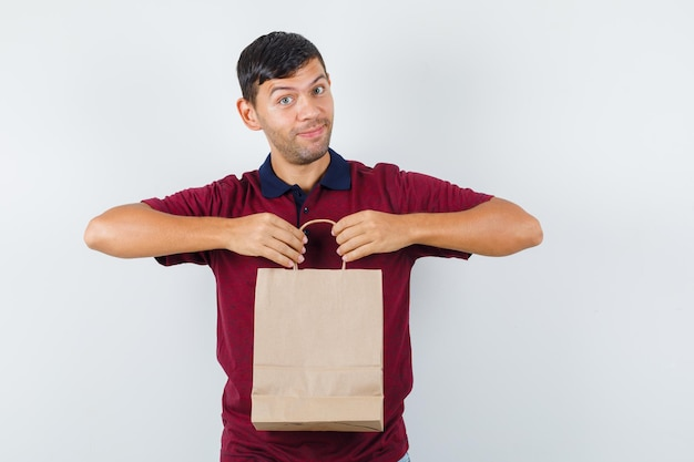 Young man holding paper bag in t-shirt and looking cheerful , front view.