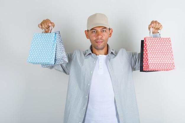 Молодой человек держит бумажные пакеты в рубашке и кепке и выглядит веселым