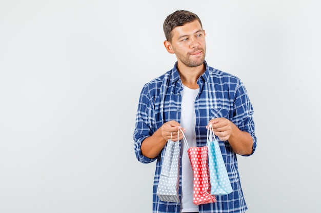 Young man holding paper bags while looking away in shirt and looking thoughtful , front view.