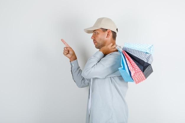 Молодой человек держит бумажные пакеты с пальцем в рубашке