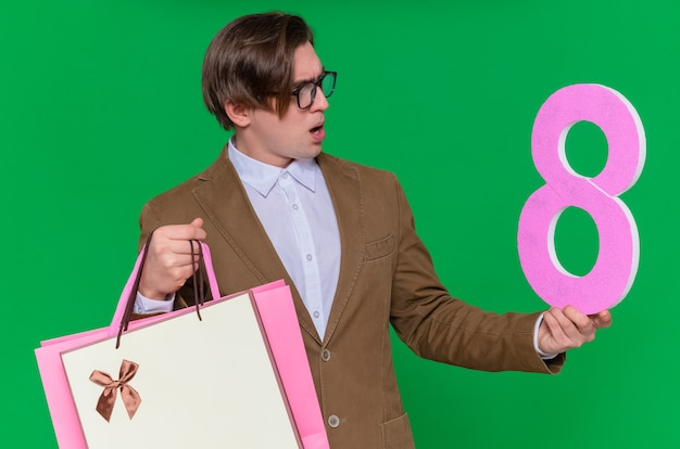 녹색 벽 위에 서있는 국제 여성의 날을 혼란스럽게보고 골판지로 만든 8 번 선물과 함께 종이 가방을 들고 젊은 남자