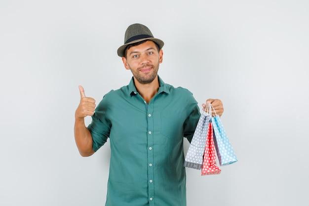 シャツに親指を立てて紙袋を保持している若い男