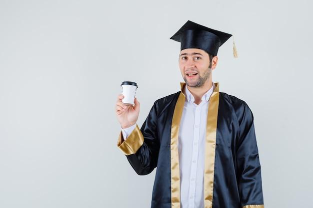 卒業式の制服を着て紙のコーヒーカップを保持し、前向きに見える若い男、正面図。