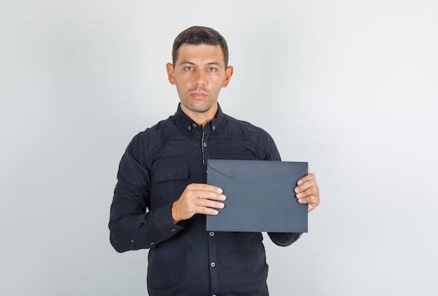 Молодой человек держит бумажный конверт в черной рубашке