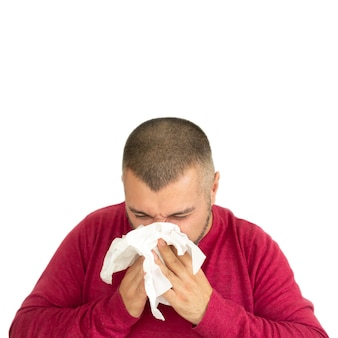 Young man holding paper handkerchief and sneezing isolated on white background