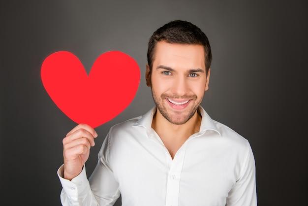 Молодой человек держит бумажное сердце