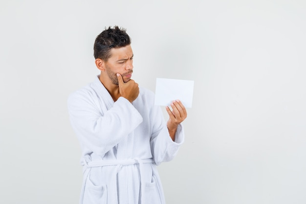 Young man holding paper sheet with hand on chin in white bathrobe and looking pensive. front view.