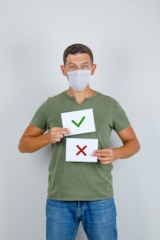 Young man holding paper sheets with options in t-shirt, jeans, mask, front view.