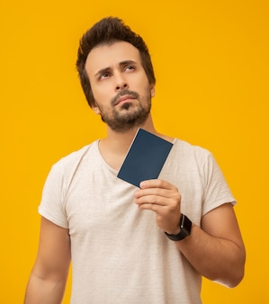 Young man holding a passport on yellow
