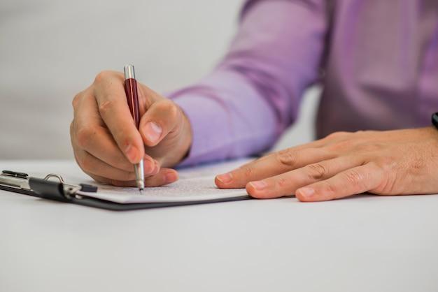 Giovane uomo in possesso di una matita, scrivendo su una carta nel diario
