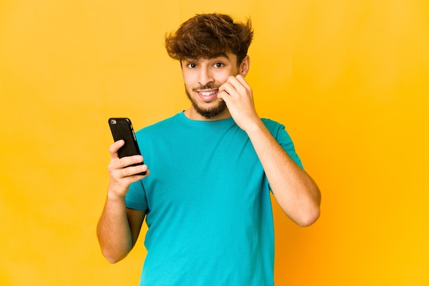 Young man holding a phone biting fingernails, nervous and very anxious