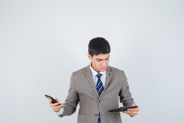 Giovane che tiene il telefono, guardando la calcolatrice in abito formale