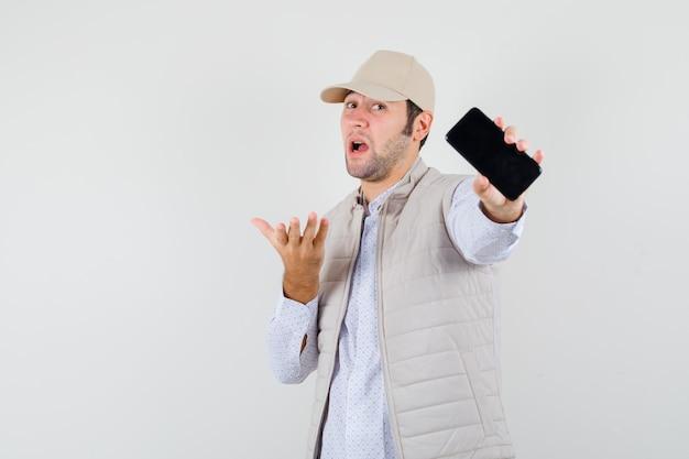 Giovane che tiene il telefono in una mano in giacca e berretto beige e sembra ottimista, vista frontale.