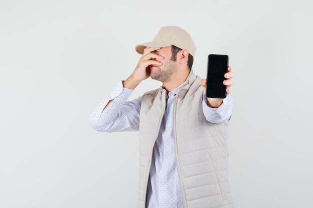 Giovane che tiene il telefono in una mano e copre parte del viso con una mano in giacca e berretto beige e sembra infastidito. vista frontale.