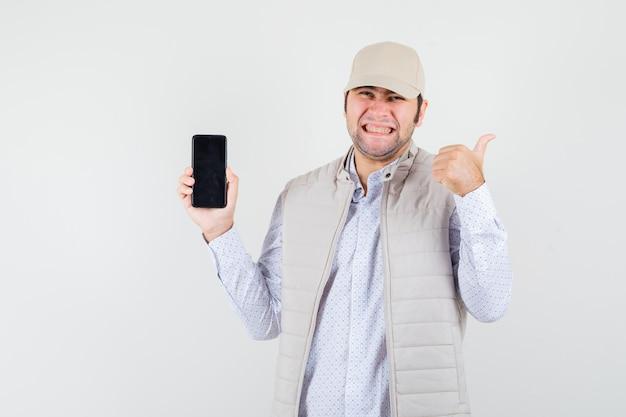 Giovane che tiene il telefono in una mano e mostra il pollice in su in giacca e berretto beige e sembra ottimista. vista frontale.