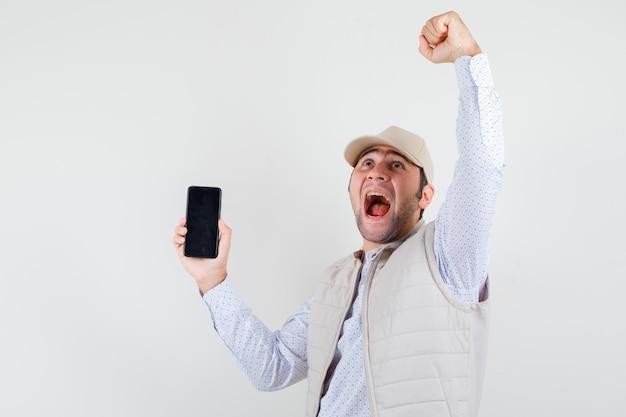 Giovane che tiene il telefono in una mano e mostra la posa del vincitore in giacca e berretto beige e sembra allegro. vista frontale.