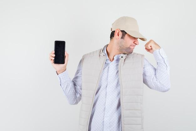 Giovane che tiene il telefono in una mano e mostra la posa del vincitore in giacca e berretto beige e sembra ottimista. vista frontale.