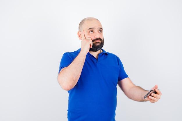 青いシャツを見上げて物思いにふける、正面図を見ながら携帯電話を保持している若い男。