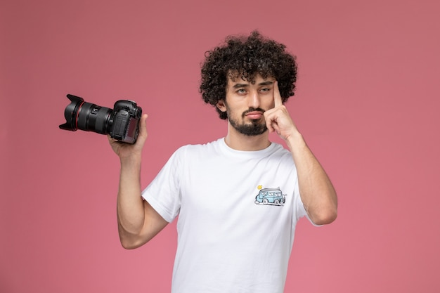 Молодой человек держит фотоаппарат и глубоко думает