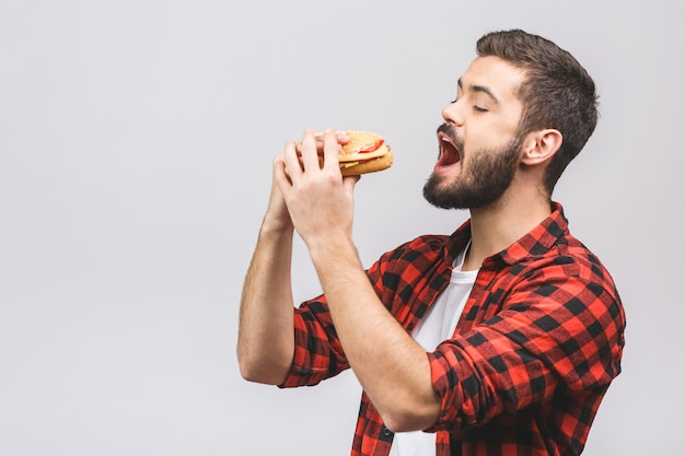 Young man holding a piece of hamburger.  diet concept isolated against white background.