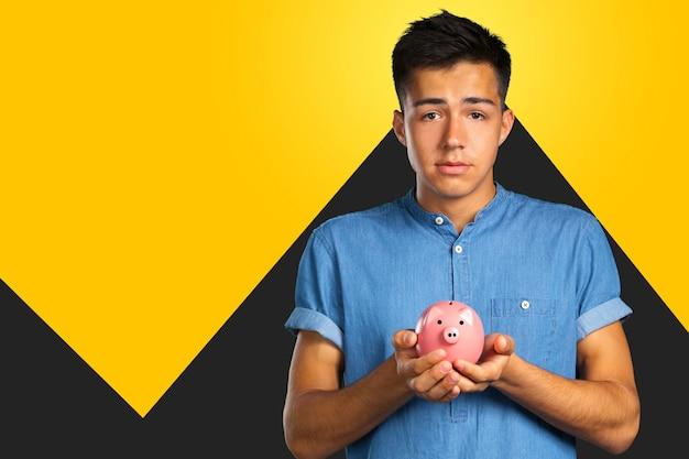 Young man holding a piggy bank