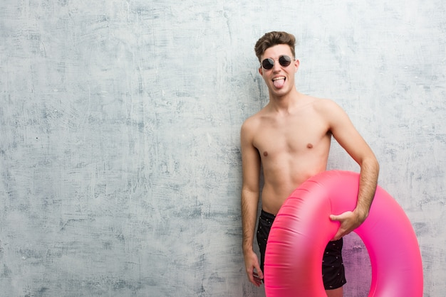 Young man holding a pink inflatable donut wearing a swimsuit funny and friendly sticking out him tongue.