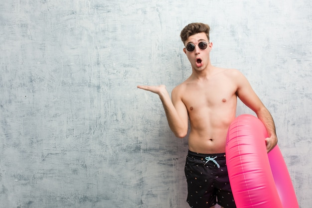 Young man holding a pink inflatable donut wearing a swimsuit impressed holding copy space on palm.